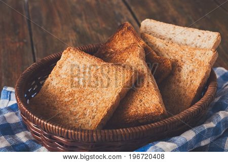 Breakfast background, white bread toasts in wicker breadbasket on checkered table napkin half covering wooden table, closeup