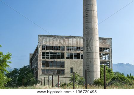 Abandoned and crumbling vintage obsolete industrial building with chimney in front of it