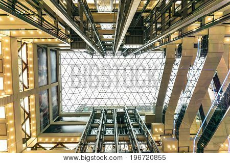 The yard is a well in a modern shopping mall or center. Look up at the glass ceiling, perspective. Elevators, escalators