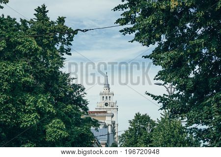 Tower of South-East Railway Administration Building in frame of green trees in Voronezh city, Russia