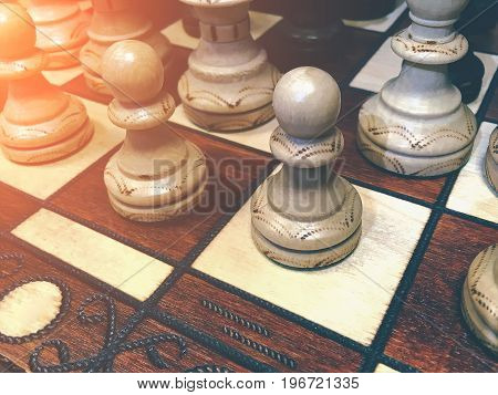 White wooden chess pieces on a chess board, toned with sun light. Chess game concept
