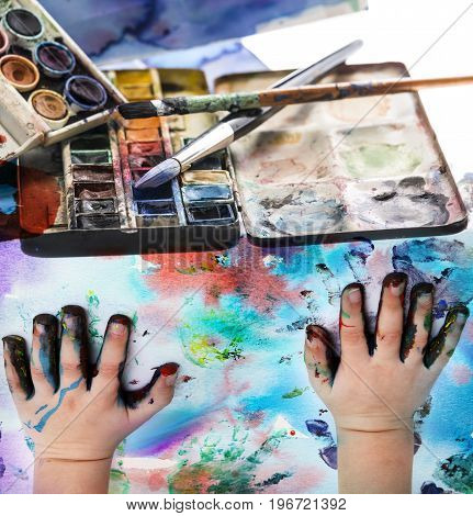 watercolors and paintbrush with children hands - art still life