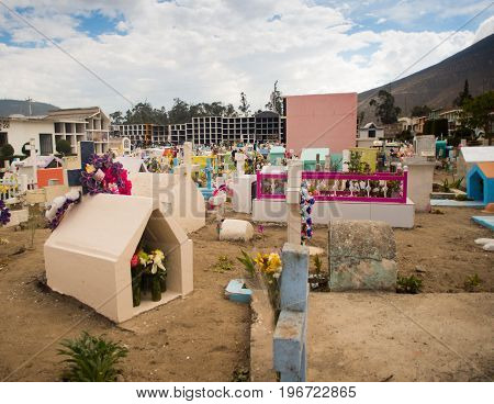 QUITO, ECUADOR- MAY 23, 2017: View of cemetery San Antonio de Pichincha, showing typical catholic graves with large gravestones, mountain background.