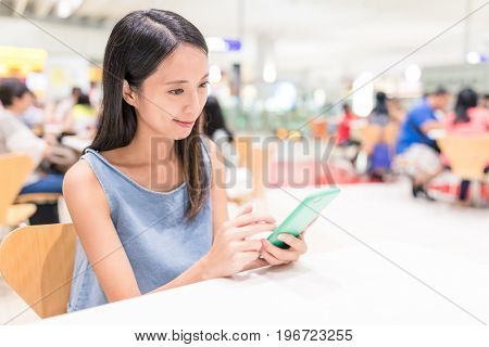 Woman working on mobile phone in shopping mall