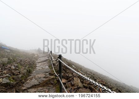 The way to the highest mountain in Krkonose National Park Snezka. Foggy windy and wet weather the view of the ridge lost in cloud.