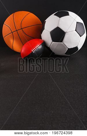 Assorted sports balls on black background. Tools for playing basketball, soccer and football, active game, healthy lifestyle concept
