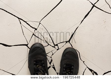 Top view of black shoes on cracked floor, copy space. Unrecognizable person in sneakers standing on fractured background