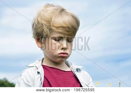 Little boy crying - isolated on blue sky background