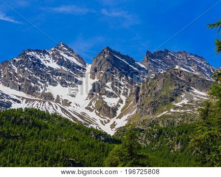 a wonderfull view of the Three Levanne,are the most famous  mountains in the National Park of Great Paradise,in Piedmont,Italy /at the beginning of summer the mountains Three Leavanne with their 3500 metres heightare covered with snow