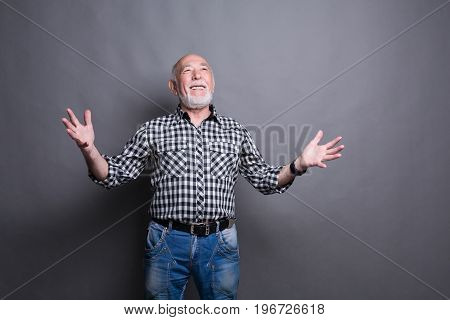 Excited senior man very glad to success, looking upwards and gesturing with hands, gray studio background