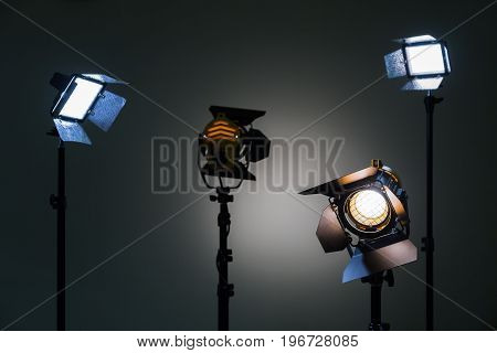Two floodlights with halogen lamps and Fresnel lens and two led lighting device. Shooting in the interior on a gray background.
