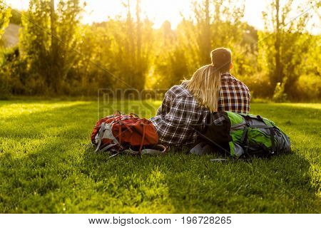 Young couple with backpacks sitting on the grass