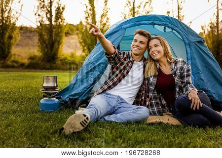 Shot of a happy couple camping on the nature and pointing to somewhere