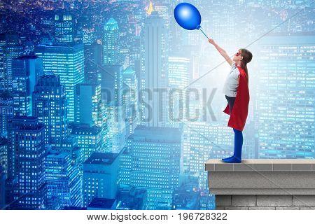 Superhero kid holding air balloon