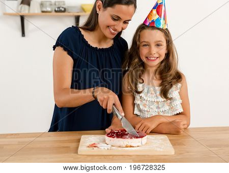 Shot of a mother and daughter cuting the cutting the birthday cake