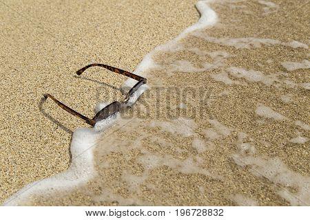 The sunglasses on beach sand and foam