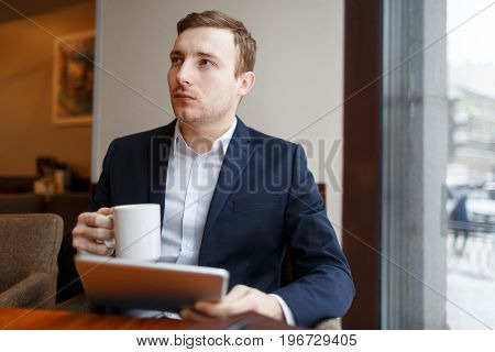 Pensive businessman with mug and touchpad networking in cafe