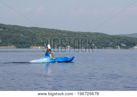 woman kayaking on a calm lake alone