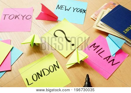 Vacation concept. Stick with question mark and sticks with names Tokyo, London, Milan, New York.