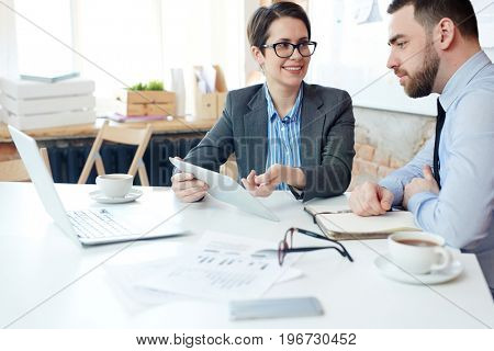 Economists discussing online project by workplace