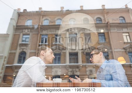 Two young co-workers having talk in urban cafe