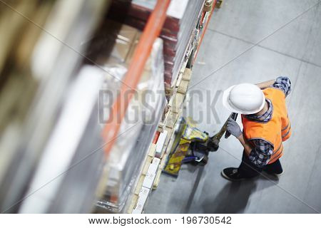 Above view of warehouse loader picking up heavy pellets  using forklift cart