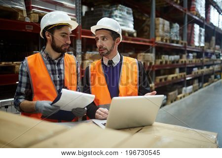 Portrait of two warehouse workers doing inventory of stock, manager talking to loader while using laptop to enter data from goods listsStocktaking in Warehouse