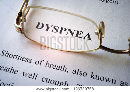 Paper with word dyspnea (shortness of breath) and glasses.