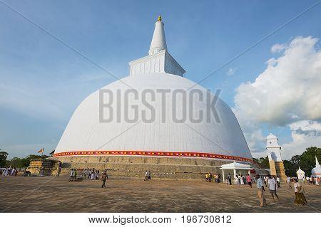 ANURADHAPURA, SRI LANKA - MAY 18, 2011: Unidentified people visit Ruwanwelisaya stupa. Ruwanwelisaya is a sacred place for Buddhists and one of the largest stupas in the world.