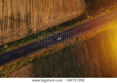 Aerial view of cars on the road through countryside in sunset drone point of view