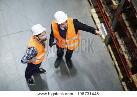 Above view of two warehouse workers doing stocktaking counting merchandise on tall shelves, pointing up