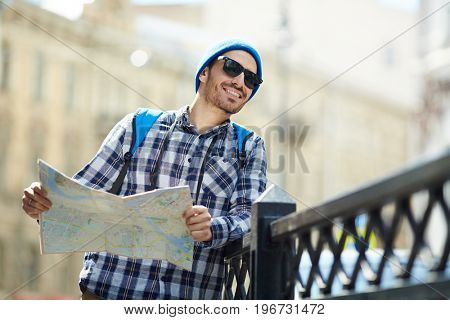 Portrait of modern young man  holding map traveling alone in Europe sightseeing in streets of old city