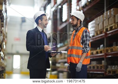 Portrait of warehouse manager wearing business suit talking to loader in aisle between tall shelves with packed goods