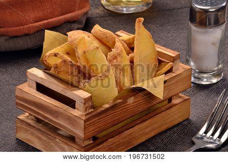 fried potatoes wood basked on table.