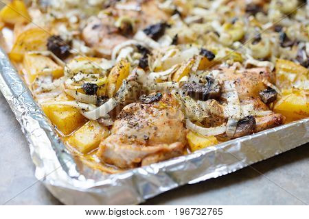 Oven roasted chicken thighs and yukon gold potatoes with leeks and herbs on a baking sheet lined with aluminum foil