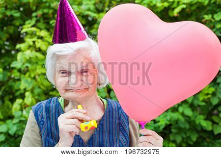 Picture of a happy elderly woman celebrating birthday holding a heart shaped balloon an blowing a whistle outdoor