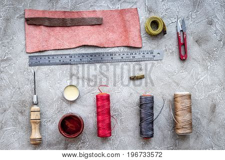 Leather workshop. Tanner's tools on grey stone background top view.