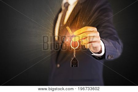 Formal man hand over shiny keys with dark background
