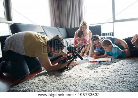 Happy Young Family Playing Together at home on the floor using a tablet and a children's drawing set
