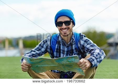 Portrait of happy young man on solo trip in Europe, sitting on green lawn holding map to look up directions and looking at camera , smiling