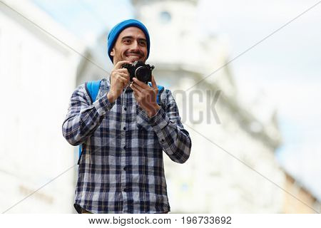 Portrait of modern tourist on solo trip in Europe, young man standing in street of old city taking pictures with photo camera and smiling