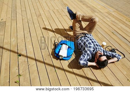 Handsome young man lying on wooden dock planks enjoying sunlight on tourist trip with photo camera and backpack nearby