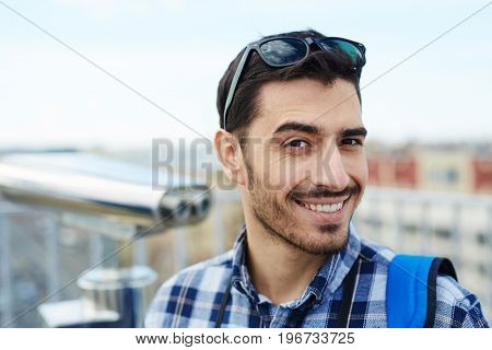 Portrait of handsome young man smiling cheerfully at camera while standing on rooftop viewing platform against panoramic city view and coin-operated binoculars in background