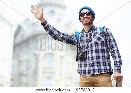 Portrait of modern young tourist on solo trip in Europe, smiling  man standing in street of old city hailing a taxi