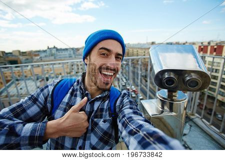 Portrait of happy young man showing thumbs up to camera taking selfie photo