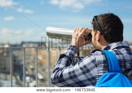 Back view portrait of contemporary male  tourist looking over city from viewing platform on the roof, using coin operated binoculars