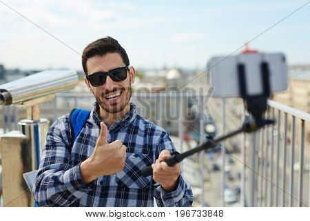 Portrait of handsome young man taking selfie photo while standing on rooftop against panoramic city view and coin-operated binoculars in background