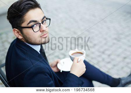 Posh man in suit having tea outdoors