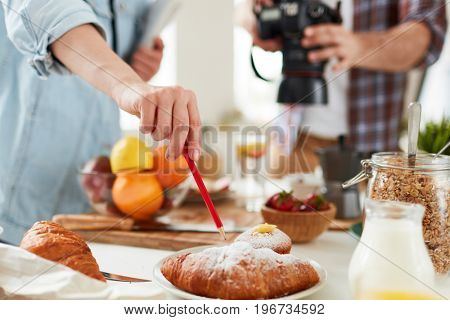 Food-stylist pointing at fresh croissant during working process