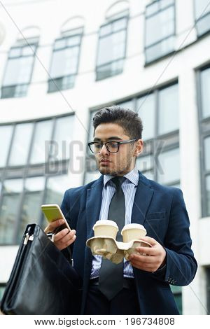 Young manager with briefcase and drinks texting outdoors